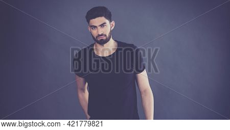 Portrait of handsome middle eastern man with hand in his pocket against grey background. fashion studio shoot concept
