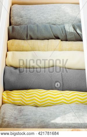 A Stack Of Neatly Stacked Womens Clothing In Yellow And Gray Colors In A Wooden Chest Of Drawers