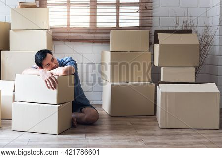 Asian  Man Being Stressed And Tired With Many Parcels Placed All Around, Which He Prepared For Movin