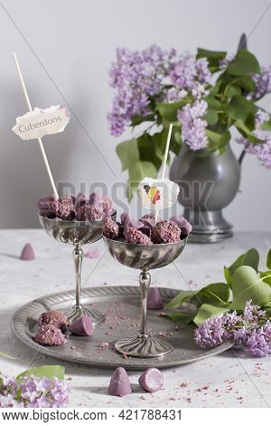 Belgian Sweets Cuberdon And Pralines In Silver Glasses, Spring Still Life With Lilac Flowers And Fla