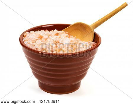 Coarse red Himalayan salt in brown bowl with small wooden shovel isolated on white background