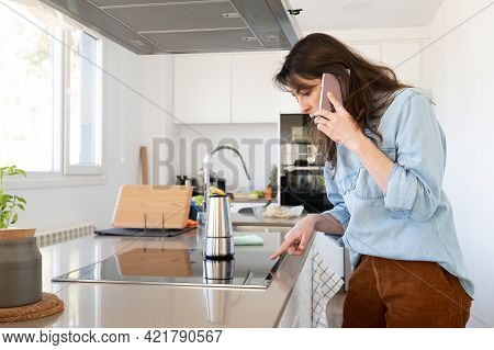 Busy Working Woman Talking On The Phone And Preparing Coffee In Her Kitchen At Home