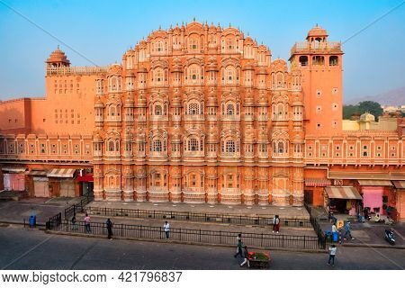 Famous landmak pink Hawa Mahal Palace of winds with people, road traffic and city transport. Mughal art cultural heritage famous tourist attraction. Jaipur, Rajasthan, India