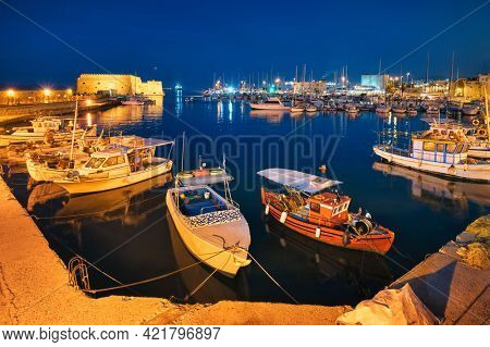 Venetian Fort castle in Heraklion and moored Greek fishing boats in port, Crete Island, Greece in the night