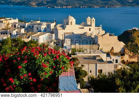 Picturesque scenic view of Greek town Plaka on Milos island over red geranium flowers and Orthodox greek church. Plaka village, Milos island, Greece. Focus on flowers