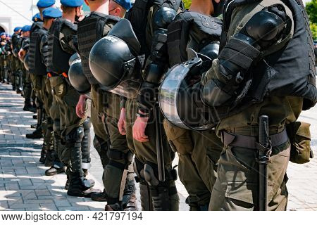 A Perspective Photo Of A Row Of Armed Special Police Workers With Helmets In Their Hands. Ready To C