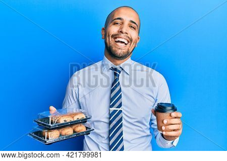 Hispanic adult business man holding take away coffee and sweets smiling and laughing hard out loud because funny crazy joke.