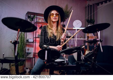Beautiful Young Woman In Black Hat And Eyeglasses Playing Electronic Drums Indoors. Female Musician