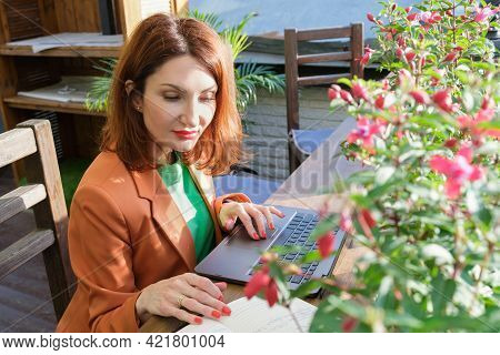 Red-haired Young Woman In A Blazer Sits On The Open Veranda Of A Restaurant With A Laptop And A Pape
