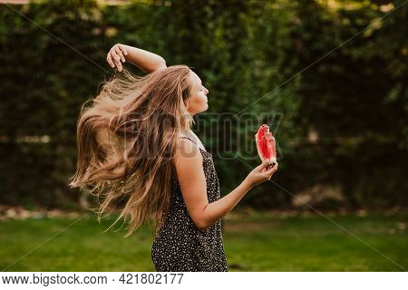 Beautiful Young Teen Girl With Long Hair In Blue Summer Overalls Posing With Big Slice Of Watermelon