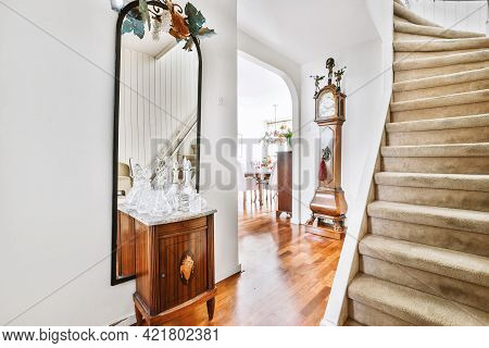 Classic Mirror With Small Cabinet And Floor Clock In White Hall Of House With Wooden Parquet Floor A