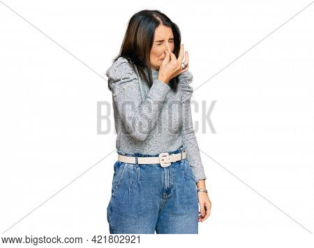 Middle age brunette woman wearing casual clothes smelling something stinky and disgusting, intolerable smell, holding breath with fingers on nose. bad smell