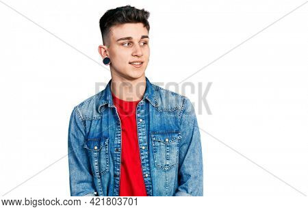Young caucasian boy with ears dilation wearing casual denim jacket looking away to side with smile on face, natural expression. laughing confident.