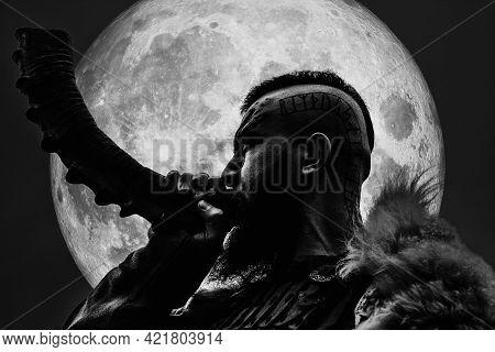 Brutal Armed Viking Warrior Blowing Horn Outdoors.