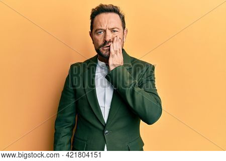 Middle age man wearing business suit touching mouth with hand with painful expression because of toothache or dental illness on teeth. dentist