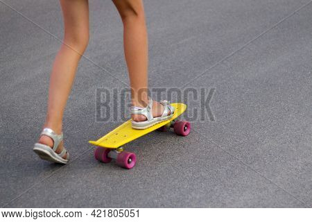 Defocus Girl Playing On Yellow Skateboard In The Street. Caucasian Kid Riding Penny Board, Practicin