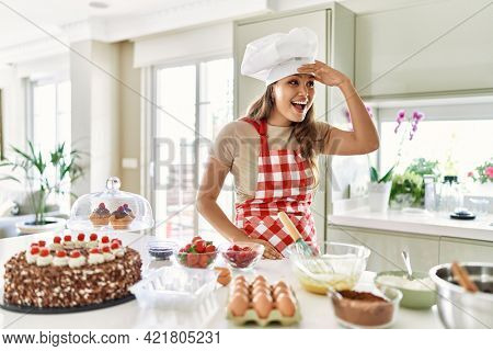 Beautiful young brunette pastry chef woman cooking pastries at the kitchen very happy and smiling looking far away with hand over head. searching concept.