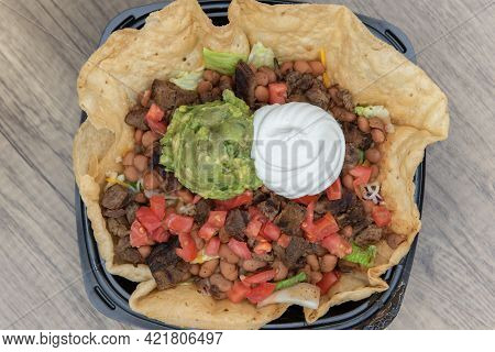 Overhead View Of Steak Taco Salad Served In A Crispy Tostada Bowl, Topped With Sour Cream And Guacom