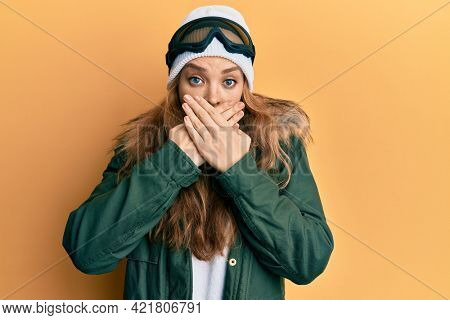 Beautiful blonde caucasian woman wearing snow wear and sky glasses shocked covering mouth with hands for mistake. secret concept.