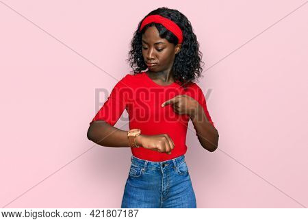 Beautiful african young woman wearing casual clothes in hurry pointing to watch time, impatience, upset and angry for deadline delay