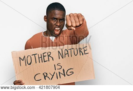 Young african american man holding mother nature is crying protest cardboard banner annoyed and frustrated shouting with anger, yelling crazy with anger and hand raised