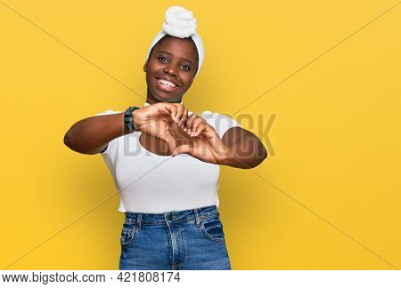 Young african woman with turban wearing hair turban over isolated background smiling in love doing heart symbol shape with hands. romantic concept.