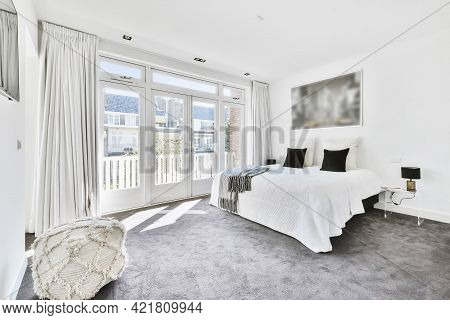 Interior Of Modern Spacious Master Bedroom With Big Bed Under City Photo And Gray Carpet Flooring In