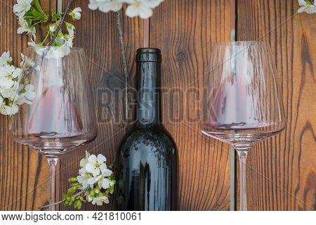 An Open Bottle Of Wine And Two Glasses On A Wooden Table With Cherry Blossoms. Classic Wine And Cher