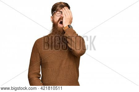 Young irish redhead man wearing casual clothes and glasses yawning tired covering half face, eye and mouth with hand. face hurts in pain.