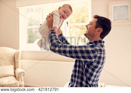 Loving Father Lifting Baby Son In Air As They Play Game At Home Together