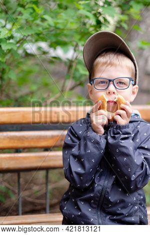 Funny Boy With Glasses And A Bagel. Hilarious Photo Of A Child Wearing Glasses. A Boy With Poor Eyes
