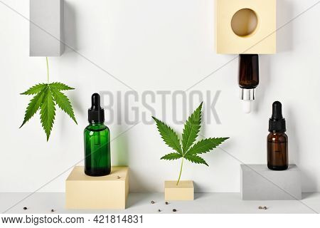 Different Glass Bottles With Cbd Oil And Cannabis Leaves On Abstract Geometric Podiums. Cosmetics Cb