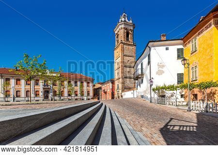 Town square, old belfry and colorful houses under blue sky in La Morra, Piedmont, Northern Italy.