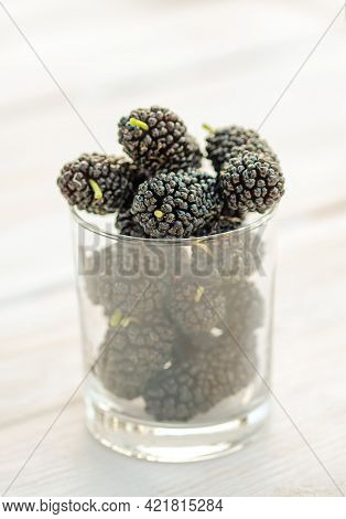 Fresh Black Mulberry In A Jar Glass Or Bowl On The Wooden Table. Mulberry Close-up. Organik Freshly