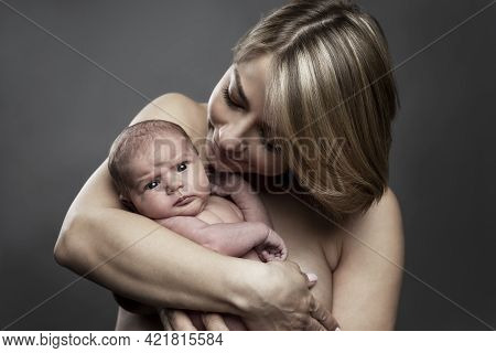 A Young Mother Holds A Newborn Baby 1 Week Old In Her Arms. Love And Tenderness In Breastfeeding. Cl