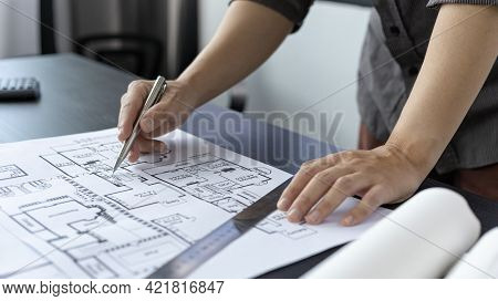Architectural building design and construction plans with blueprints, Young man was designing a buil