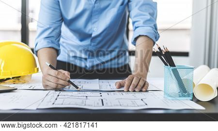 Engineer and Architect concept, Man uses a ruler to measure the floor plan on the blueprint, Buildin