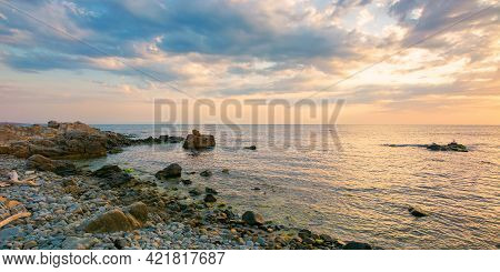 Summer Vacation Scenery By The Sea At Sunrise. Calm Water Washes Pebble Beach With Stones And Boulde