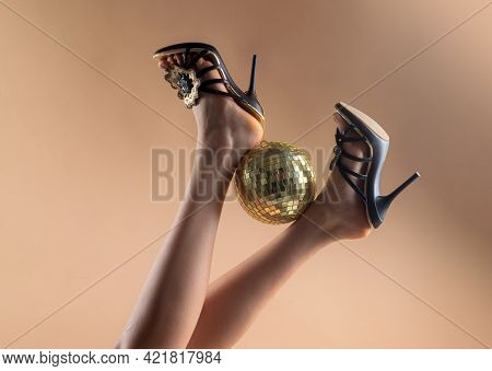 Gold Disco Ball On High Heels. Sexy Legs. Disco Party. Woman Legs With Gold Disco Ball. Celebrate Co