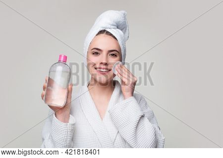 Girl With Micellar Water. Beautiful Woman With Towel On Head, Micellar Water And Cotton Pad Isolated