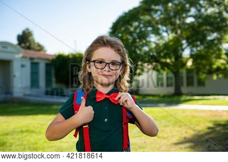Cheerful Little School Boy In School Uniform With Backpack Standing Near School. Back To School. Kid