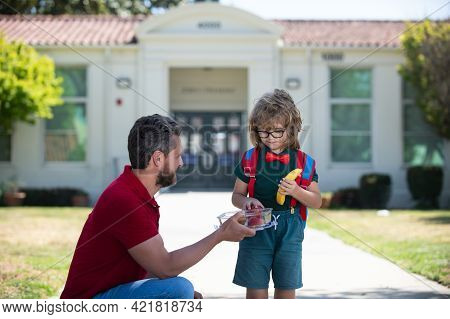 School Boy Going To School With Father. Little Schoolboy Eating Tasty Lunch Outdoors. School Lunch F