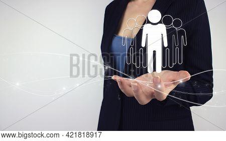 Team Leader Concept. Hand Hold Digital Hologram Group Of People On Grey Background. Marketing Segmen