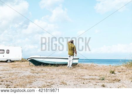 Man Looks Out To Sea At The Beach Near His White Camper Van Parked By The Sea And A Boat. Tourist Se