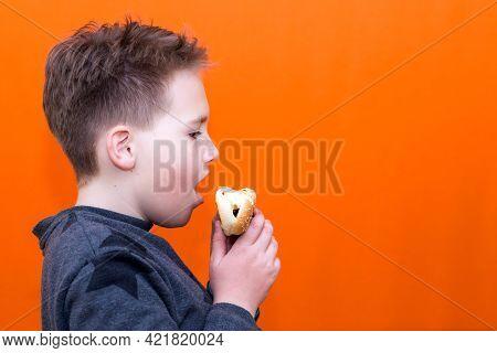 Handsome 10 Yers Old Boy Holding And Biting Hot Dog Indoors Orange Studio Background Image.side View