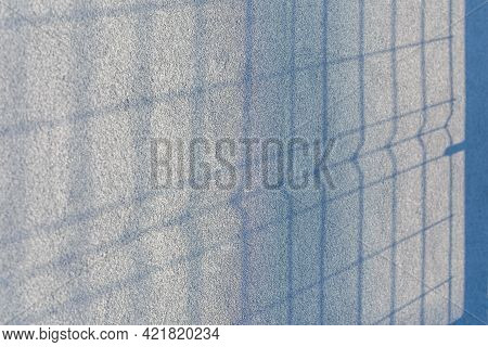 The Shadow Of The Fence On The Gray Blue Plastered Wall. Fence With Sunlight And Shade. Modern Desig