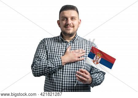 White Guy Holding A Flag Of Serbia And Holds His Hand On His Heart Isolated On A White Background Wi