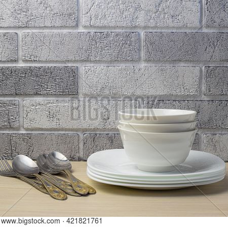 White Crockery And Cutlery On The Background Of A Light Brick Wall. Copy Space.