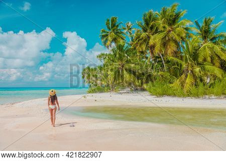 Luxury paradise private island woman traveller relaxing walking on remote beach in the Rangiroa atoll, Tuamotu islands, French Polynesia. Bikini girl on cruise excursion.
