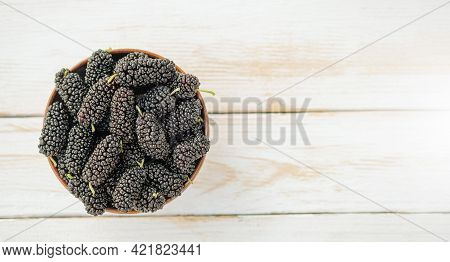 Fresh Black Mulberry In A Wooden Bowl On The White Wooden Table. Mulberry Top View Close-up.organik